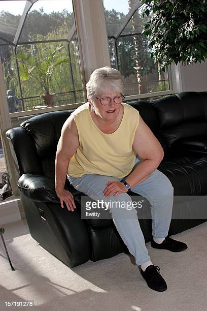 achy woman on couch at home holding her knee in pain - fat old lady stock photos and pictures
