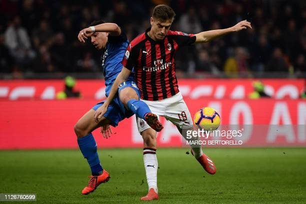 ACMilan's forward Krzysztof Piatek from Poland fights for the ball with Empoli's midfielder Ismael Bennacer from France during the Italian Serie A...
