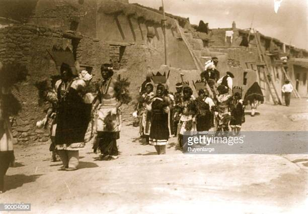 Acoma men and women in ceremonial dress make their way down a street beside pueblo buildings