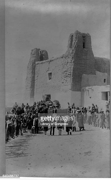 Acoma Pueblo people march in a procession carrying crosses outside the adobe Roman Catholic mission Acoma New Mexico USA | Location Acoma New Mexico...