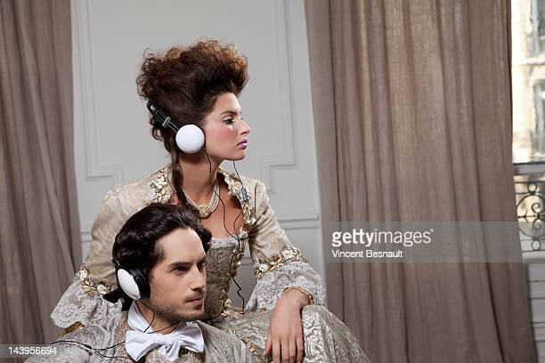 Acouple in 18th centruy costume using headphones