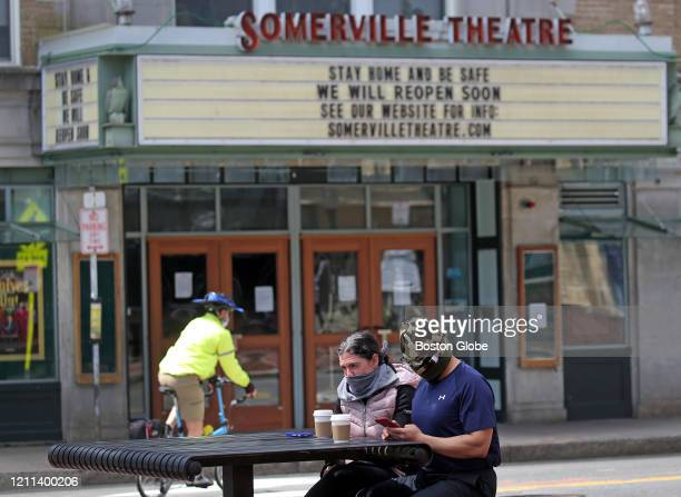 Acouple seated by a table wear masks in Davis Square in Somerville, MA on April 29, 2020. Somerville will require face masks in public beginning...