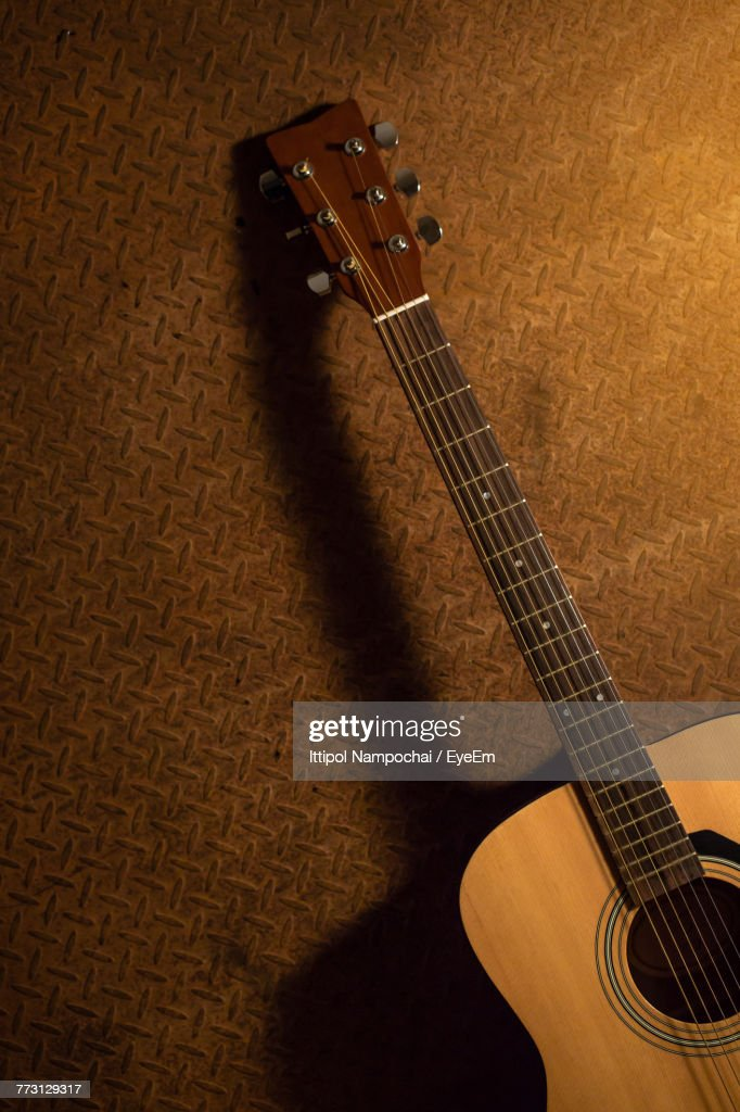 Acoustic Guitar By Brown Wall : Stock Photo