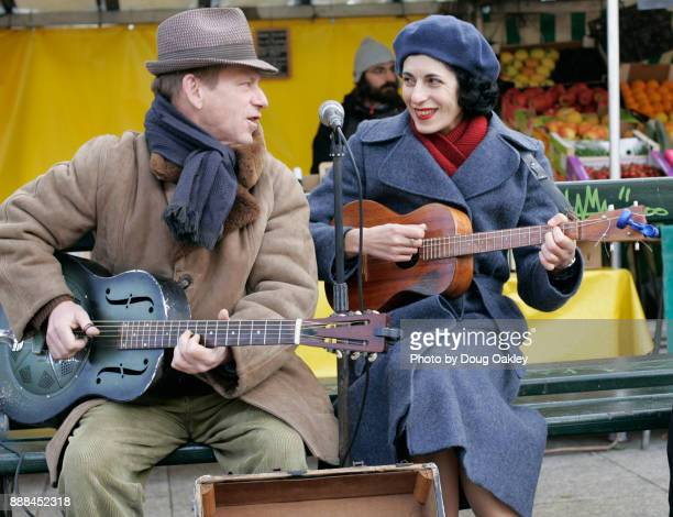 Acoustic guitar duo perform at Marche Bastille open air market in Paris