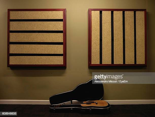 acoustic guitar on floor against wall - alessandro miccoli stockfoto's en -beelden