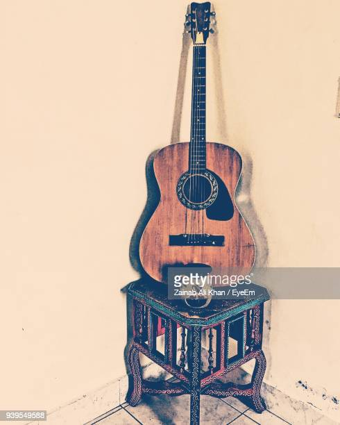 Acoustic Guitar On Table By Beige Wall