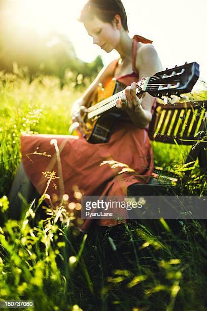 Joven mujer tocando guitarra acústica
