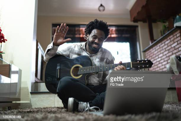 acoustic guitar teaching through a video call, waving to laptop at home - musician stock pictures, royalty-free photos & images