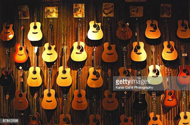 acoustic guitars on a wall - acoustic guitar stock pictures, royalty-free photos & images