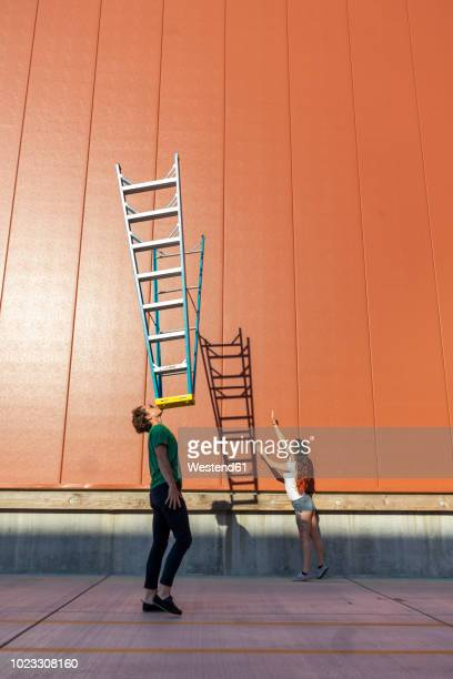 acrobat balncing ladder on his face while colleague is trying to catch its shadow - homem pegando mulher imagens e fotografias de stock