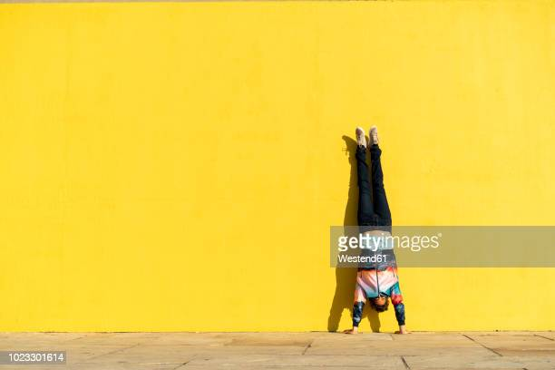 acrobat doing handstand in front of a yellow wall - yellow stock pictures, royalty-free photos & images