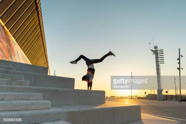 acrobat doing handstand on stairs at sunrise - handstand stock pictures, royalty-free photos & images