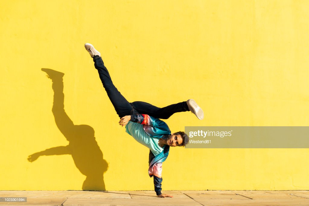Acrobat doing movement training in front of a yellow wall : Stock Photo