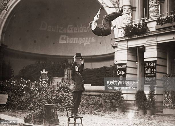 Acrobat Gerhardi Mohr somersaults over a man standing on a chair in Berlin whilst training for his feat of leaping over a house circa 1910