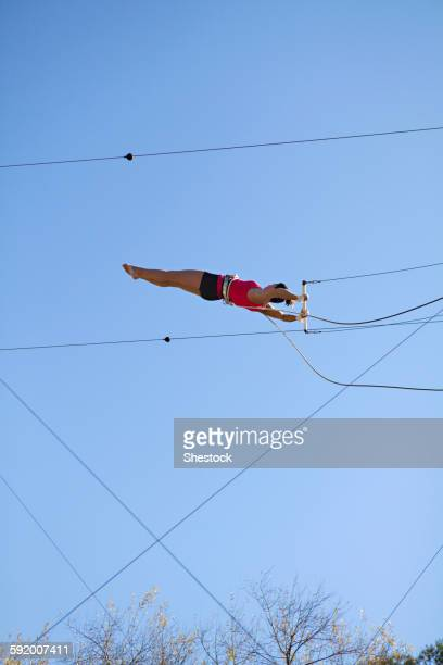 Acrobat hanging from trapeze under blue sky