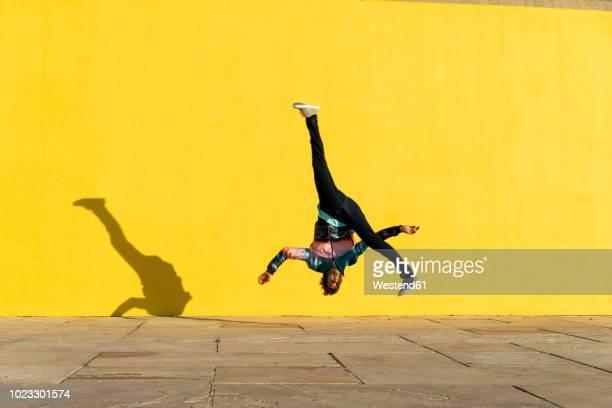 acrobat jumping somersaults in front of yellow wall - jumping stock pictures, royalty-free photos & images
