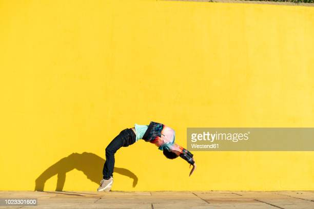 Acrobat jumping somersaults in front of yellow wall