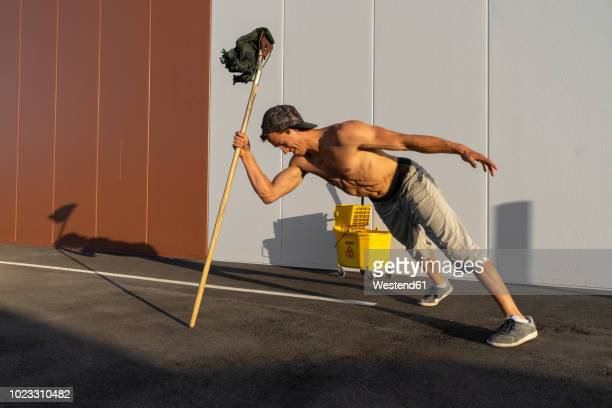 acrobat playing with cleaning bucket and mop - stunt stock pictures, royalty-free photos & images