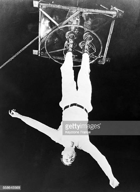 L'acrobate américain JD Pate traverse d'une gratteciel à l'autre suspendu par les pieds à une corde tendue entre les deux buildings le 15 juin 1932
