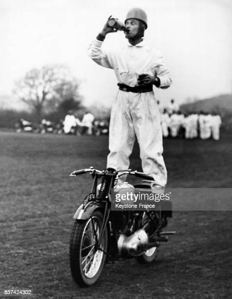UN acrobate à moto s'entraînant à Catterick Camp dans le Yorkshire boit à la bouteille tout en conservant parfaitement son équilibre debout sur sa...