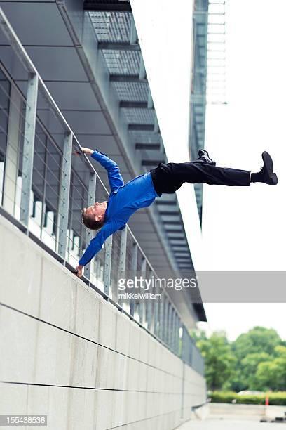 Akrobatische bussinesman ist jumping um außerhalb Bürogebäude