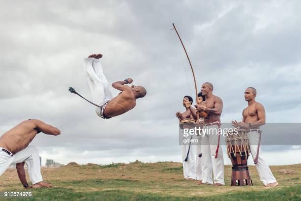 acrobatic capoeira jump at beach in salvador da bahia - capoeira imagens e fotografias de stock