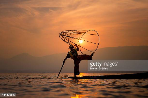 acrobatic fisherman with cone net at sunset - merten snijders stock pictures, royalty-free photos & images
