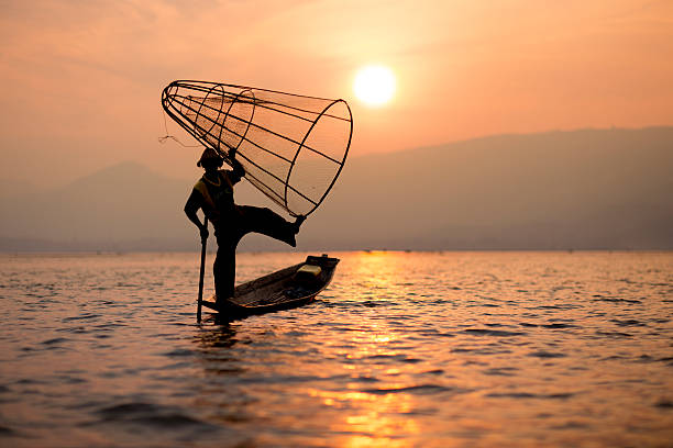 Acrobatic Fisherman With Cone Net At Sunset Wall Art