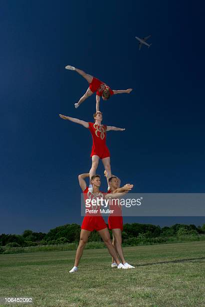 acrobatic troop performing moves - acrobatic activity stock photos and pictures