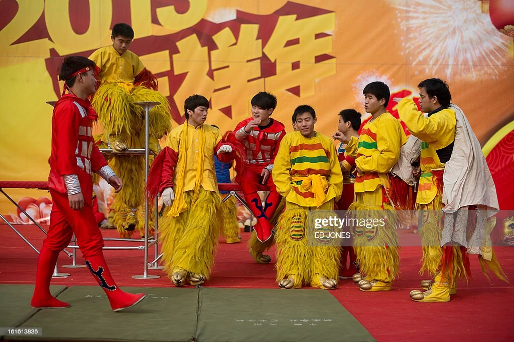 Acrobats and lion dancers wait on stage prior to a performance at a temple fair at Longtan park in Beijing on February 13, 2013