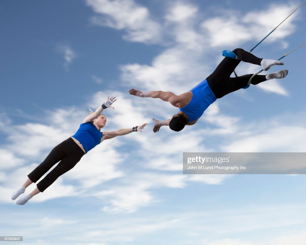 Acrobats catching each other in the air : Stock Photo