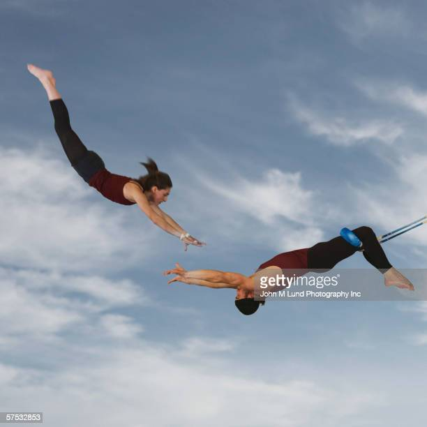 acrobats catching each other in the air - trapeze artist stock photos and pictures