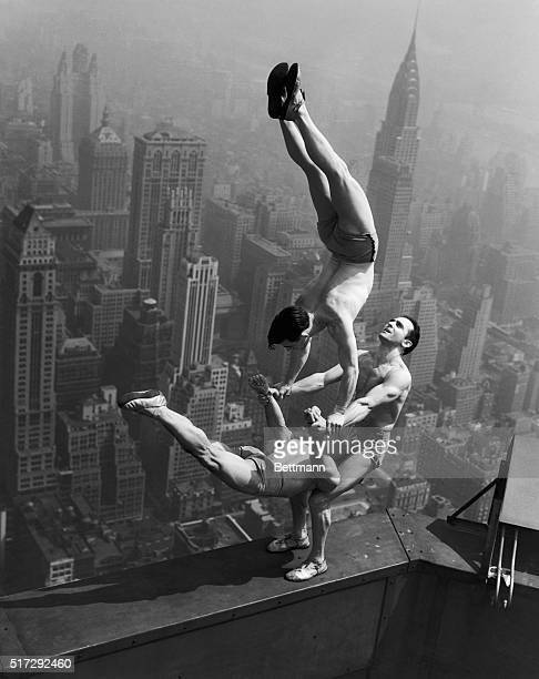 Acrobats Jarley Smith Jewell Waddek and Jimmy Kerrigan perform a delicate balancing act on a ledge of the Empire State Building in Manhattan