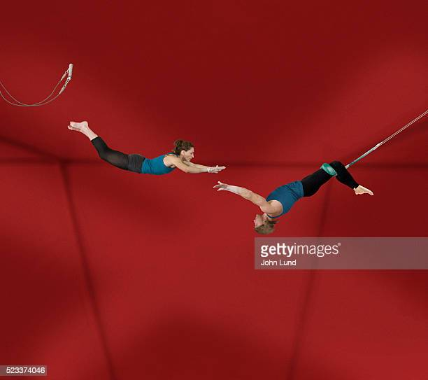 acrobats performing on trapeze - trapeze artist stock photos and pictures