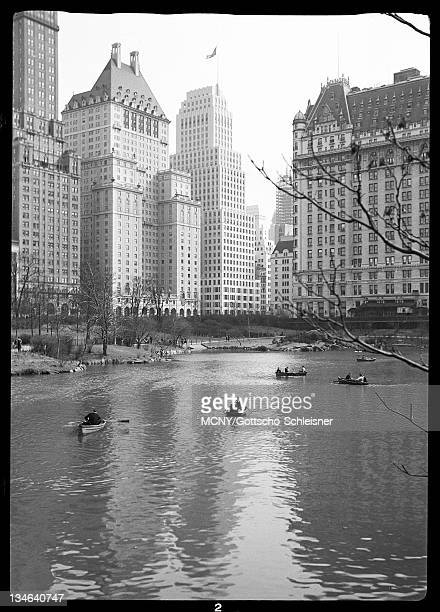 Across pond in park showing boaters, the Plaza Hotel, the Squibb Building, and the Savoy-Plaza Hotel