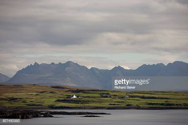 Across the calm waters of a Scottish bay isolated houses and crofts sit before the dramatic Cuillin Mountains that rise up in the distance on the...