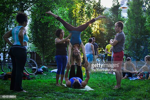 WASHINGTON DC JUNE Acroyoga practitioners Coleen Gentles left Lili Herrera 2nd from L Helena Snyder upside down Dean Hivey on back and Brian...