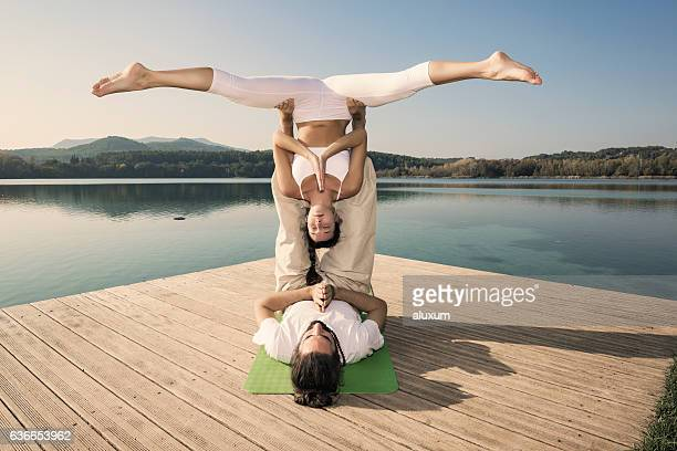 Acroyoga straddle bat pose