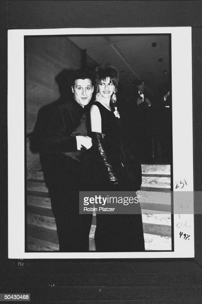 Acterss Sandra Bernhard wearing large dangling earings a fulllength black gown long leather gloves posing w designer Isaac Mizrahi at the 12th annual...