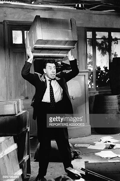 L'acteur Fernandel porte une caisse en bois circa 1960 en France