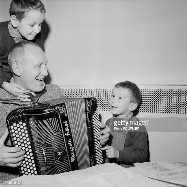Acteur français Bourvil à l'accordéon, entouré de ses fils Dominique et Philippe .