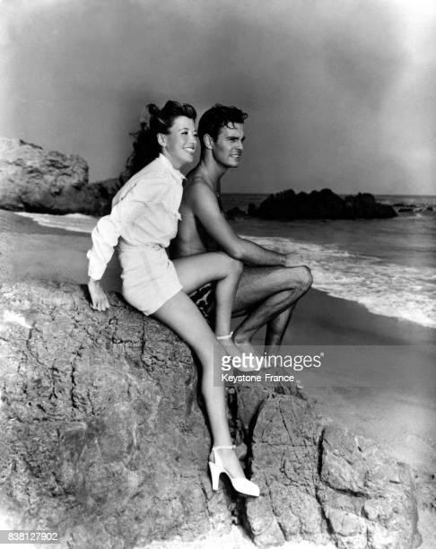 L'acteur français Louis Jourdan en compagnie de sa femme Berthe se repose sur la plage de Santa Monica à Los Angeles Californie EtatsUnis en 1946