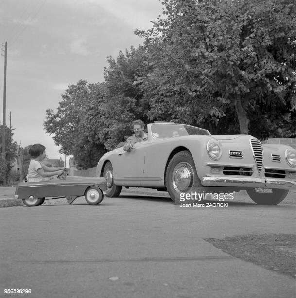 L'acteur JeanPierre Aumont et sa fille Tina font une course de voitures a Suresnes en France circa 1951 L'acteur conduit une Alfa Romeo Spider 6C...