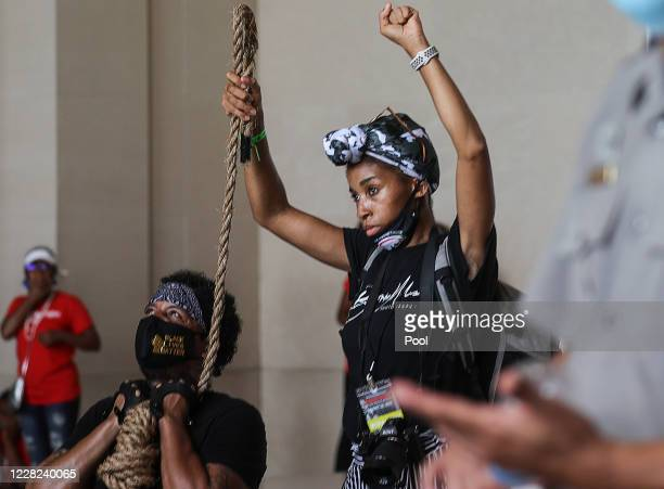 "Actiivist Jay Vegas wears a noose while posing with participants at the Lincoln Memorial as demonstrators gather for the ""Get Your Knee Off Our..."