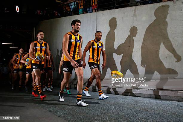 Acting Captain Ben Stratton of the Hawks leads the team onto the field flanked by Jack Gunston and Josh Gibson during the 2016 NAB Challenge match...