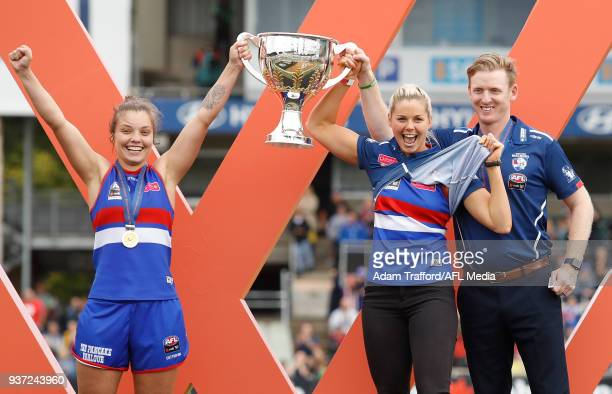 Acting captain Ellie Blackburn captain Katie Brennan and Paul Groves Senior Coach of the Bulldogs hold up the premiership cup during the 2018 AFLW...