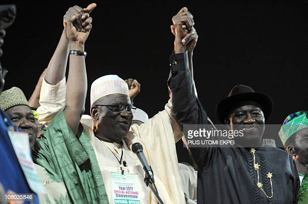 Acting chairman of the ruling Peoples Democratic Party Haliru Bello raises the hands of President Goodluck Jonathan and Vice President Namadi Sambo...