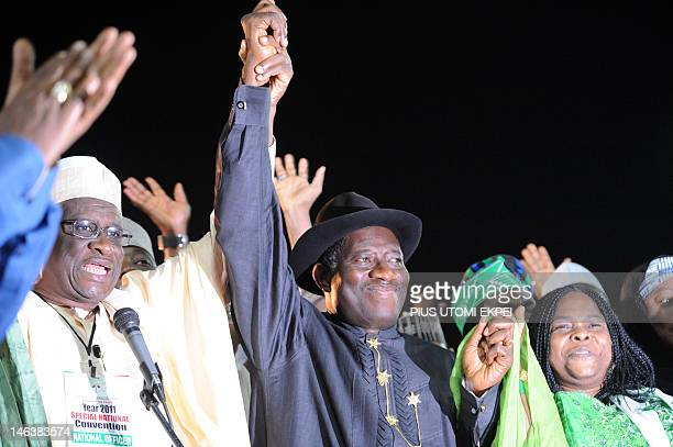Acting chairman of the ruling Peoples Democratic Party Haliru Bello raises the hands of President Goodluck Jonathan standing beside wife Patience...