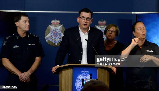 Acting chief commissioner Shane Patton looks on as Victoria's state premier Daniel Andrews speaks during a press conference in Melbourne on December...