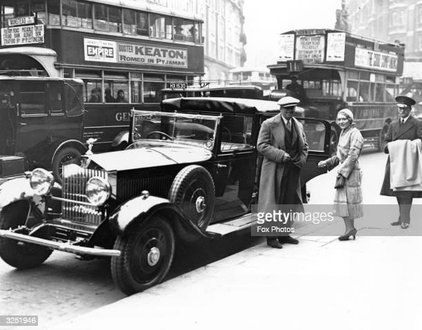 US acting couple Douglas Fairbanks and Mary Pickford beside their chauffeurdriven Rolls Royce in London